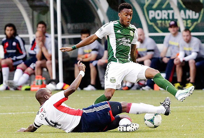 The Revolution's Kalifa Cisse slides in to take the ball from Portland Timbers' Rodney Wallace.