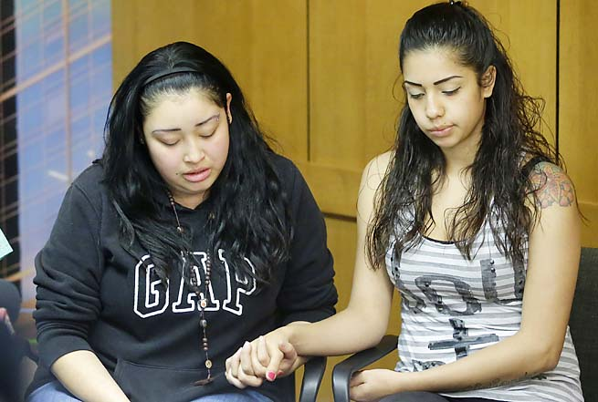 Johana Portillo (left) and sister Ana Portillo, daughters of Riccardo Portillo, hold hands during a news conference Thursday.