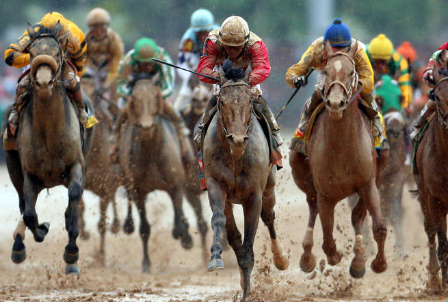 Orb (center) took first in the Kentucky Derby, giving a win to jockey Joel Rosario and trainer Shug McGaughey.