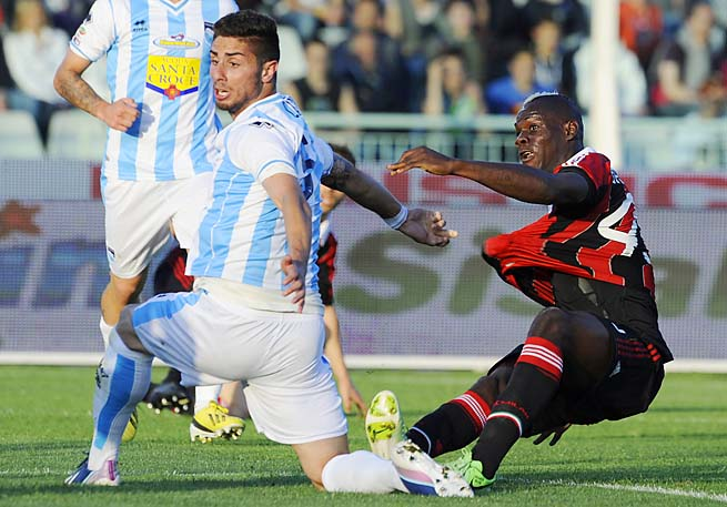 Mario Balotelli scores a goal as Pescara defender Marco Capuano vainly tries to stop him.