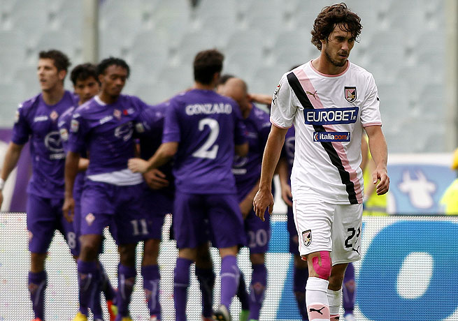 Palermo's Santiago Garcia walks away dejectedly as Fiorentina players celebrate Luca Toni's winner.