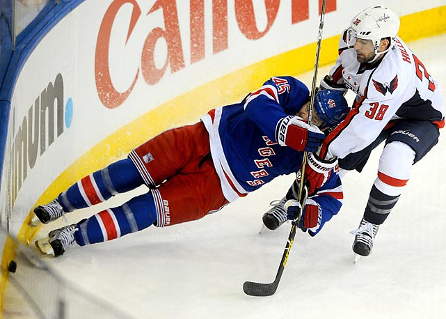 The Rangers' Arron Asham falls to the ice in a battle for the puck with the Capitals' Jack Hillen (38) during Game 6 of a first-round series Sunday.