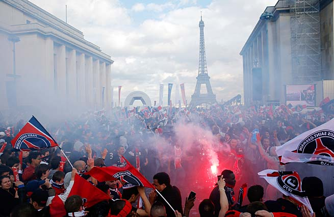 PSG fans celebrate by climbing on cars, buildings and scaffolding in Paris on Monday.