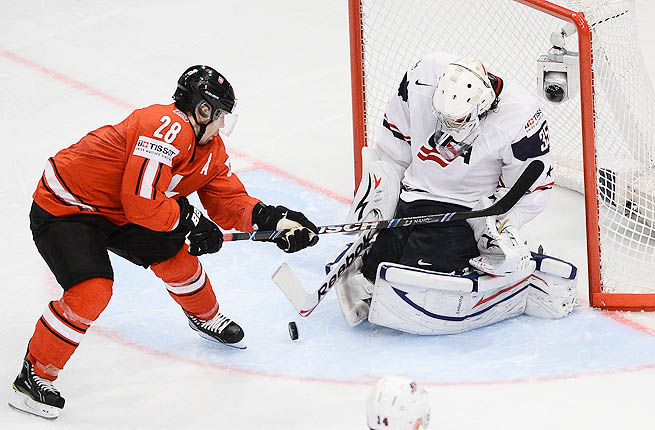 Switzerland's Martin Pluss (L) in action against US goalie John Gibson during the Ice Hockey IIHF World Championships.