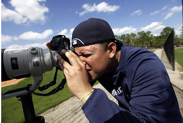 Cabrera checks out a photographers' telephoto lens during spring training in Lakeland, Fla.