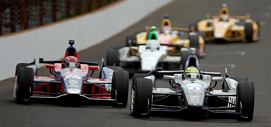 (Lead cars L-R) Marco Andretti, driver of the #25 RC Cola Chevrolet, and Tony Kanaan of Brazil, driver of the Hydroxycut KV Racing Technology-SH Racing Chevrolet, lead the field as they drive into turn one during the IZOD IndyCar Series 97th running of the Indianpolis 500.