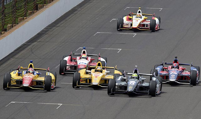 Tony Kanaan, second from right, passes Ryan Hunter-Reay on the final restart to take the lead on his way to winning the Indianapolis 500. Carlos Munoz, of Colombia, (26) finished second, Ray finished third, and Marco Andretti (25) finished fourth.