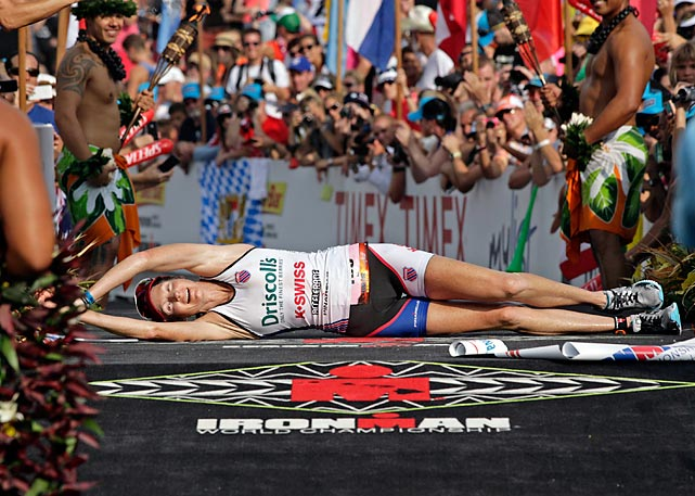 Leanda Cave, of Britain, rolls across the finish line as the women's winner of the Ironman World Championship triathlon, Saturday, Oct. 13, 2012, in Kailua-Kona, Hawaii.
