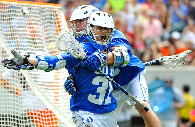Jordan Wolf (31) and Josh Dionne (8) celebrate a late goal during the NCAA men's lacrosse title game.