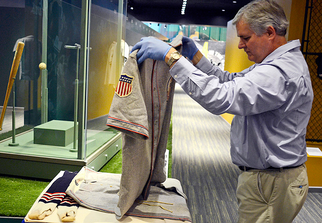 Lance Van Auken, Little League vice president, lays out the baseball uniform worn by Babe Ruth.