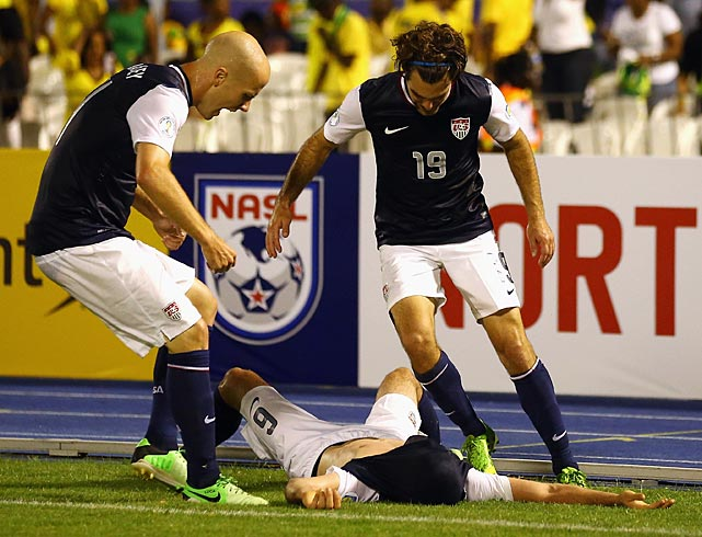 Teammates Michael Bradley (4) and Graham Zusi celebrate with Brad Evans.