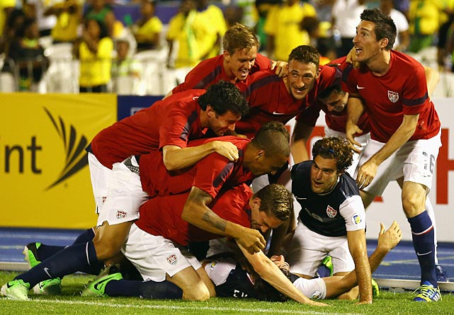 Teammates pile onto Brad Evans after he scored the game-winning goal to beat Jamaica 2-1 during the FIFA 2014 World Cup Qualifier at National Stadium in Jamaica.