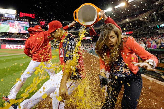 Sideline reporter Julie Alexandria and Gio González are doused by teammates following the Nationals 8-1 win over the Reds. González held Cincinnati's powerful lineup to one hit in eight innings.