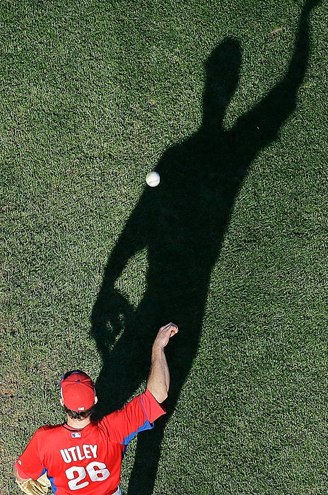 Chase Utley of the Phillies tries to out-throw his shadow during batting practice before Philadelphia's 5-4 loss to the Brewers on June 7.