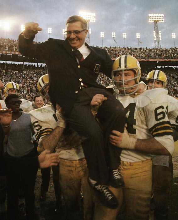 Victorious in the Super Bowl for the second consecutive year, Lombardi is carried off the field by Jerry Kramer (64).