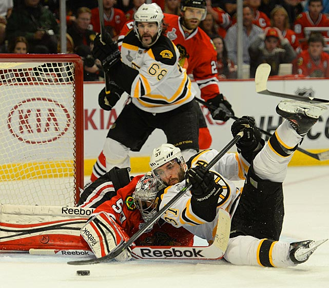 Bruins alternate captain Patrice Bergeron collides with Blackhawks goaltender Corey Crawford, who stopped 51 of the 54 shots he faced.