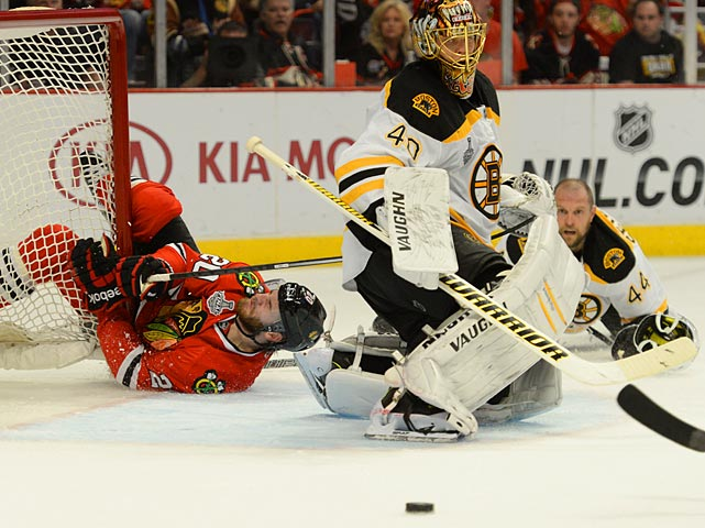 Chicago's Brandon Saad and Boston's Dennis Seidenberg fall to the ice as Tuukka Rask protects the net for the Bruins.