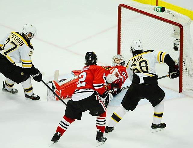 Patrice Bergeron and Jaromir Jagr try to capitalize on an opportunity against Blackhawks goalie Corey Crawford.