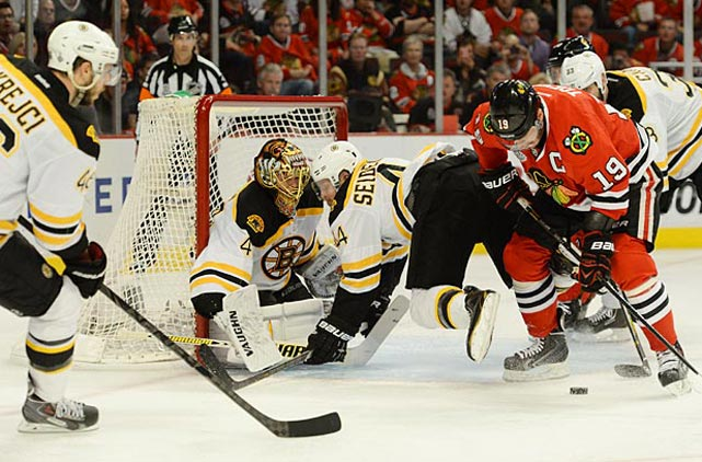 Jonathan Toews tries to control the puck to get a shot off on Bruins goalie Tuukka Rask.