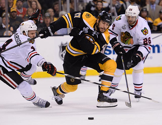 Chicago's Niklas Hjalmarsson (left) and Michal Handzus shadow Boston's Milan Lucic, who had a rough start to the evening. During warm-ups, he collided with teammate Zdeno Chara, sending the Bruins captain to the dressing room for stitches.