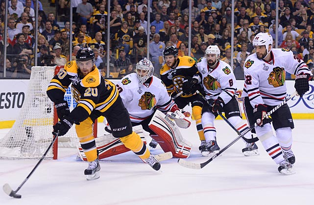 Boston's Daniel Paille (20) corrals the puck at the side of Chicago's net. Three of Paille's four goals during this postseason have been game-winners. Before this year, he'd lit the lamp four times in 46 postseason games.