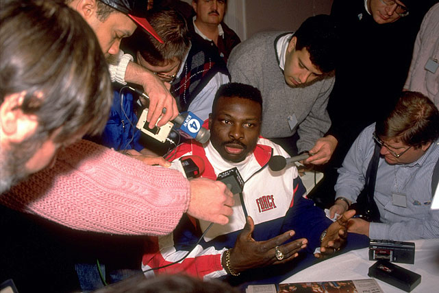 Smith is surrounded by media during a press conference before Super Bowl XXVI.
