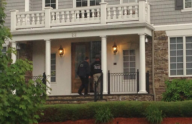 Police enter Aaron Hernandez's home on Tuesday evening as they investigated a possible homicide.