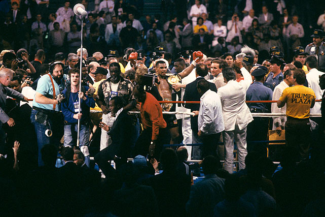 Tyson wears three title belts in celebration of his victory.