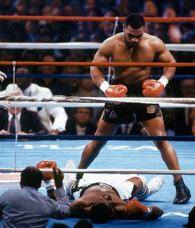 Tyson stands over Spinks victoriously, having needed only eight punches to finish him off for the title.