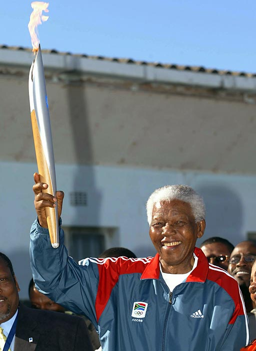 Mandela holds the Olympic Flame as part of the 2004 Olympic Torch Relay.