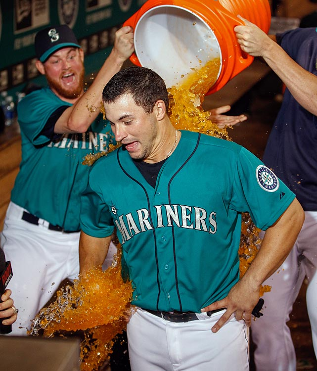 Mike Zunino is doused by teammates, including Charlie Furbush (left), following the Mariners 5-4 win over the Cubs. Zunino had the game-winning hit in the 10th inning.