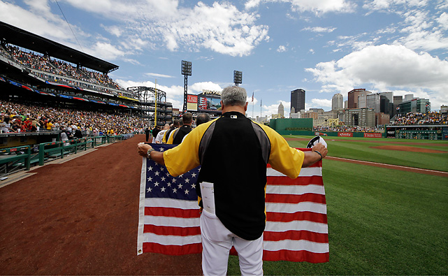 Clint Hurdle holds an American flag during the national anthem before the Fourth of July game between the Pirates and Phillies.