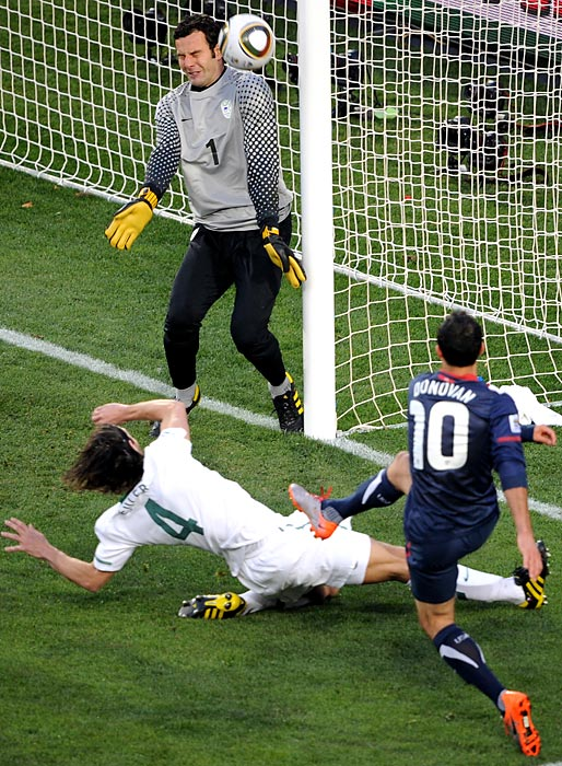 Donovan shoots and scores past Slovenia's goalkeeper Samir Handanovic and defender Marko Suler during their Group C first-round match at the 2010 World Cup.
