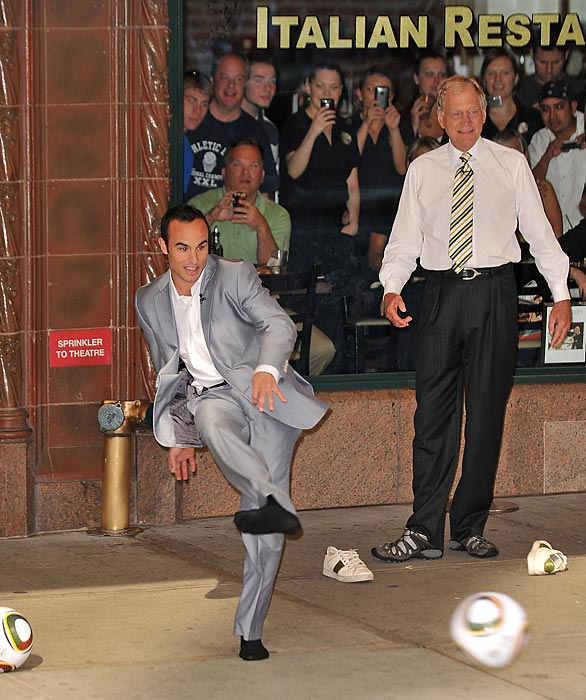"Donovan and David Letterman take turns trying to kick a ball into the open window of a taxi outside the Ed Sullivan Theater for ""The Late Show With David Letterman""."