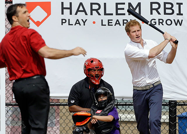 Yankees first baseman Mark Teixeira reacts to a hit by Prince Harry after pitching him a baseball during a visit to the Harlem RBI youth sports and school program in New York.