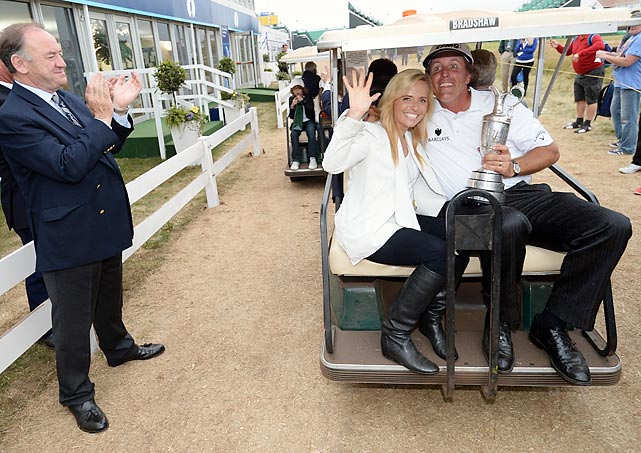 The giddy British Open champ and his spouse bid you farewell as they exit with the valuable merchandise Mr. Mickelson received for participating in the big event.