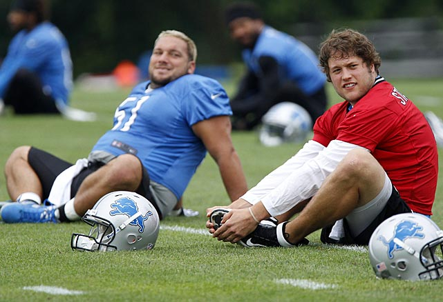 Detroit Lions quarterback Matthew Stafford, right, stretches with center Dominic Raiola in Allen Park, Mich.