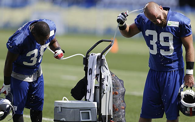 New York Giants cornerback Trumaine McBride, left, and safety Tyler Sash cool off at camp in East Rutherford, N.J.