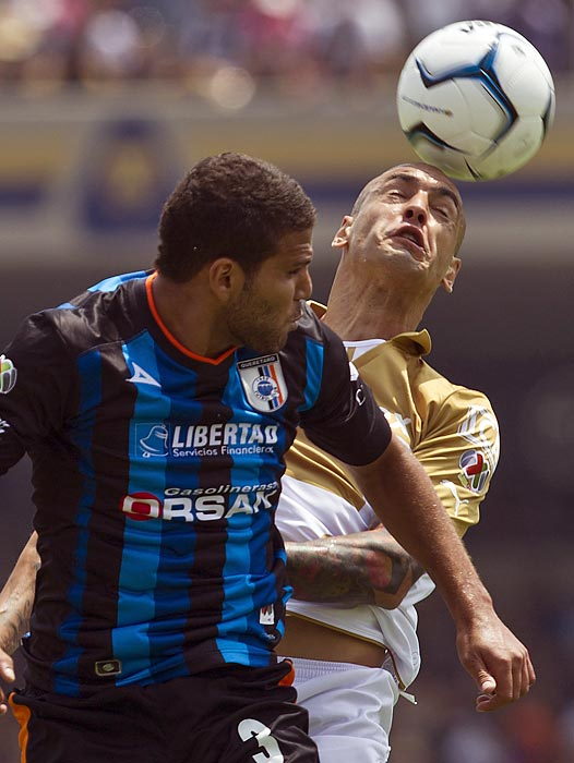 Pumas' Ariel Nahuelpan (right) fights for a header with Queretaro's Oswaldo Henriquez during a Mexican league match in Mexico City on July 28. Queretaro won 3-0.