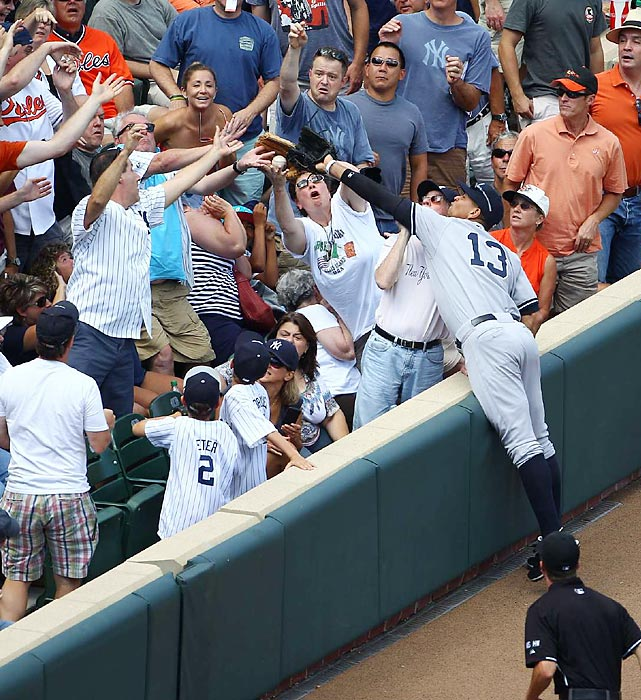 The Yankees third baseman can't quite reach this foul ball into the Camden Yards crowd in September 2012.