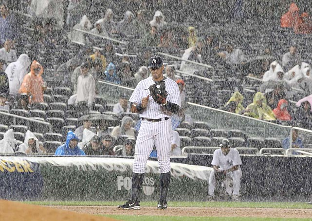 Rodriguez stands in the driving rain during Game 1 of the AL Divisional Series against the Tigers in 2011.