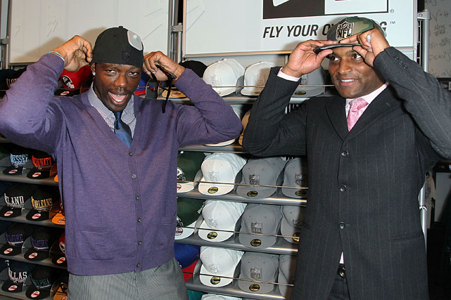 Owens and Amani Toomer try on some hats following the NFL Shop at Draft ribbon cutting on April 2, 2012 in New York City.
