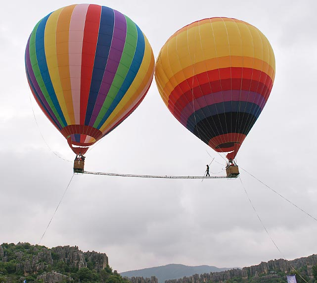 Exelon Kyle walks on a tightrope extended between two hot-air balloons in Kunming, in southwest China's Yunnan province, on July 30, 2013 . Kyle took 38.35 seconds to complete the 'hot air balloon 18 meters fast walking' and created another Guinness World Record.