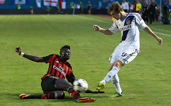AC Milan's Mbaye Niang, who scored the first goal, slides against the Galaxy's Sean Franklin.