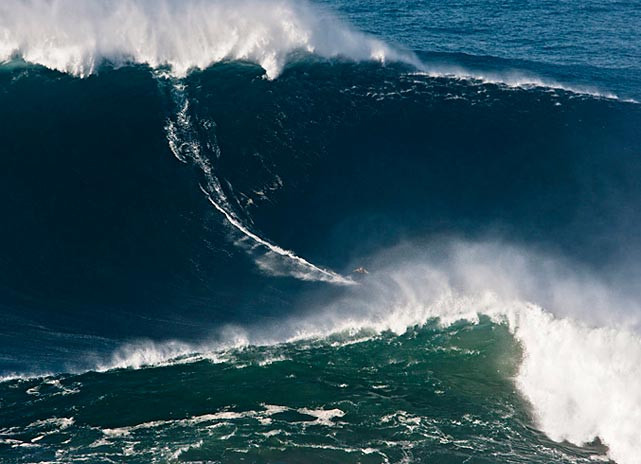 Hawaii's Garrett McNamara surfs what has been determined as the tallest wave ever ridden at Praia do Norte beach near Nazare, Portugal. Portugal's navy awarded McNamara its Medalha Naval de Vasco da Gama in a ceremony in Lisbon.
