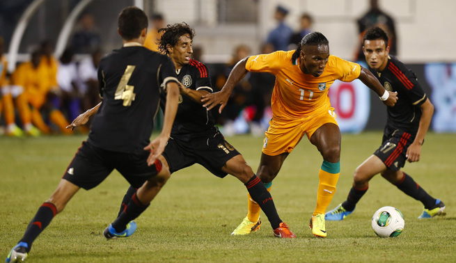Ivory Coast's Didier Drogba dribbles between three Mexico defenders during Wednesday's game.