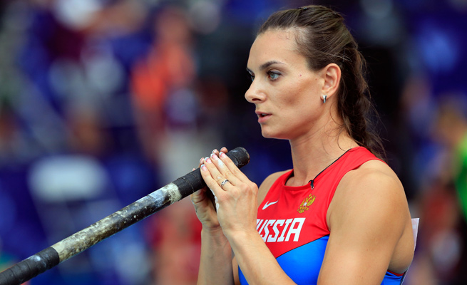 Russian pole vaulter Yelena Isinbayeva won her third world title Tuesday before voicing her support for her country's new anti-gay law.