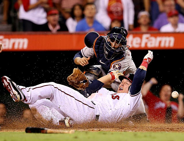 Mike Trout slides home with the tying run in the seventh inning as Astros catcher Jason Castro can't hold on to the throw.