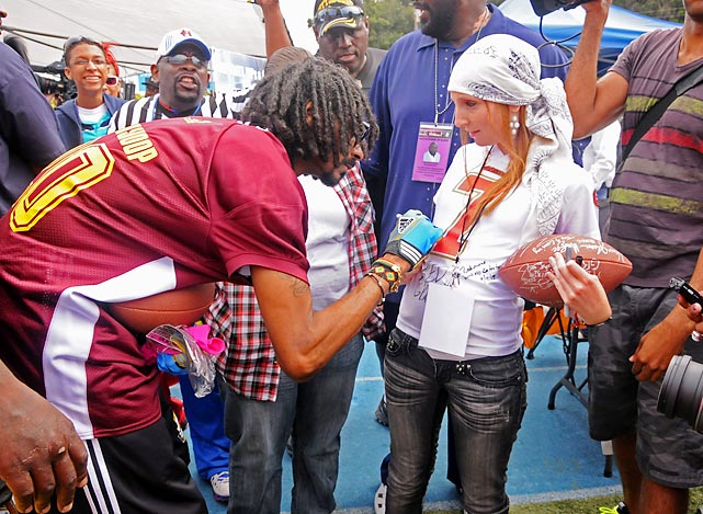 Sign of the times: The ubiquitous hip-hop artiste affixes his scrawl to a cancer survivor's shirt at the First Annual Celebrity Flag Football Game in Pacific Palisades, Calif.