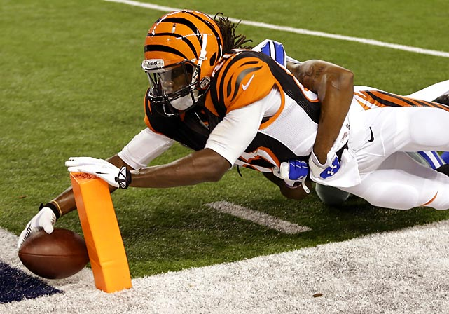 Cincinnati Bengals wide receiver Cobi Hamilton puts the ball into the end zone for a touchdown as Dallas cornerback B.W. Webb holds on.